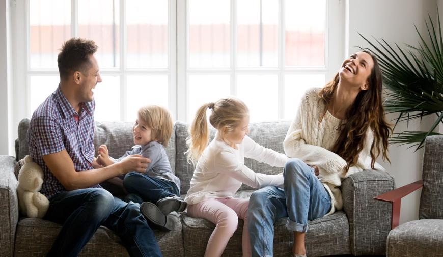 This image shows a family laughing together on a couch.
